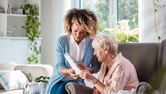 Senior woman speaking with caretaker holding a paper document in The Monarch at Richardson senior living facility in Texas